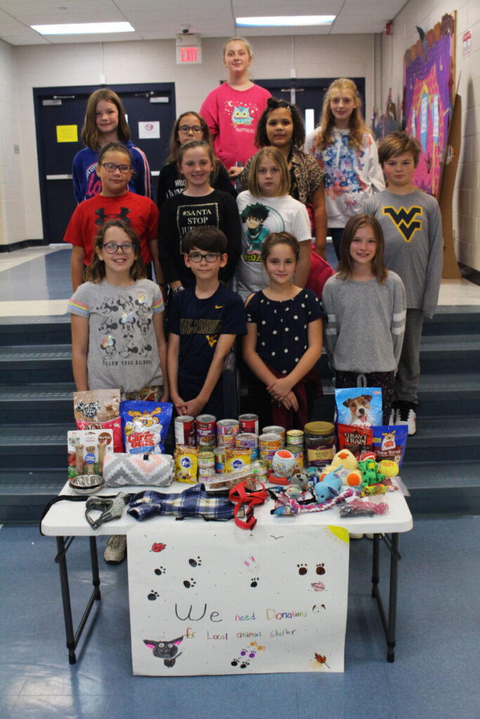 Thirteen members of the Central Elementary Kindness Club gather around the donations given for the Marshall County Animal Shelter, including food, treats, blankets, leashes and toys.