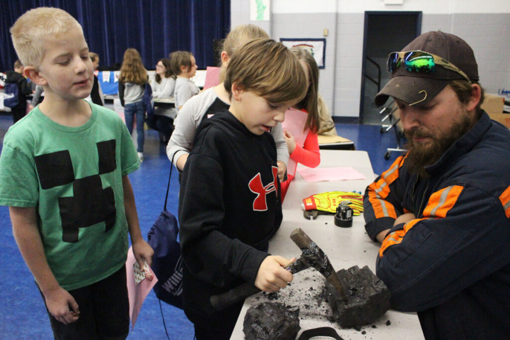 From left: Central Elementary school 3rd grader Jimmy Moore watches his classmate Jamie Wilken chip away at a piece of coal while coal miner Austin Payne shows the students what it's like to work underground.