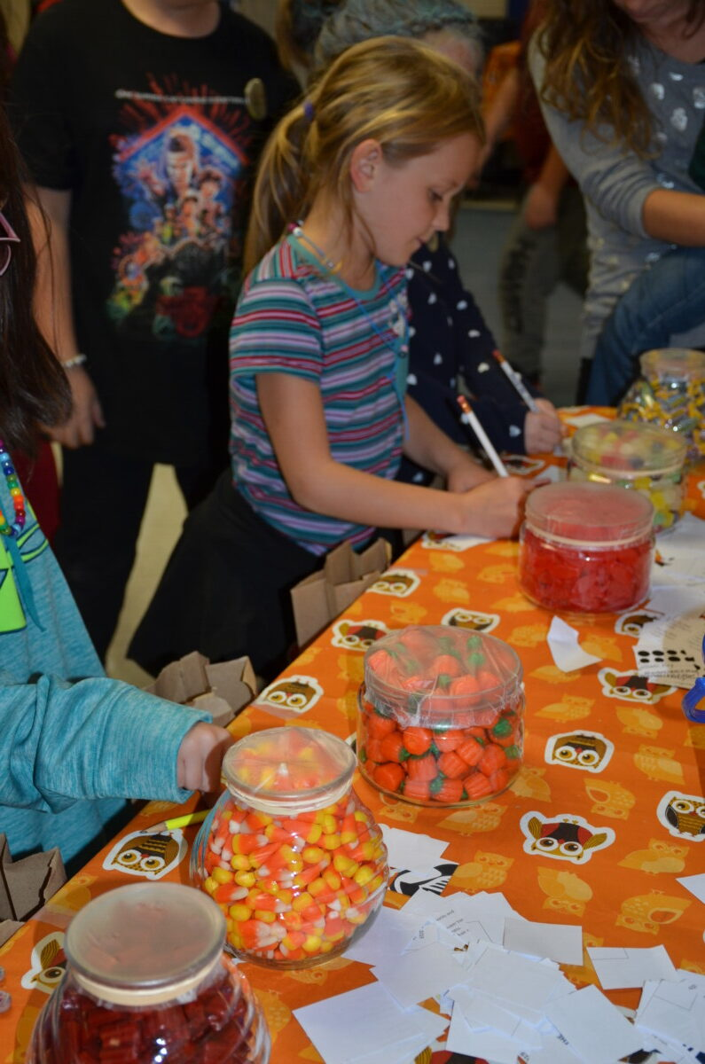 Students mark their guesses at the guess how many game during the fall festival