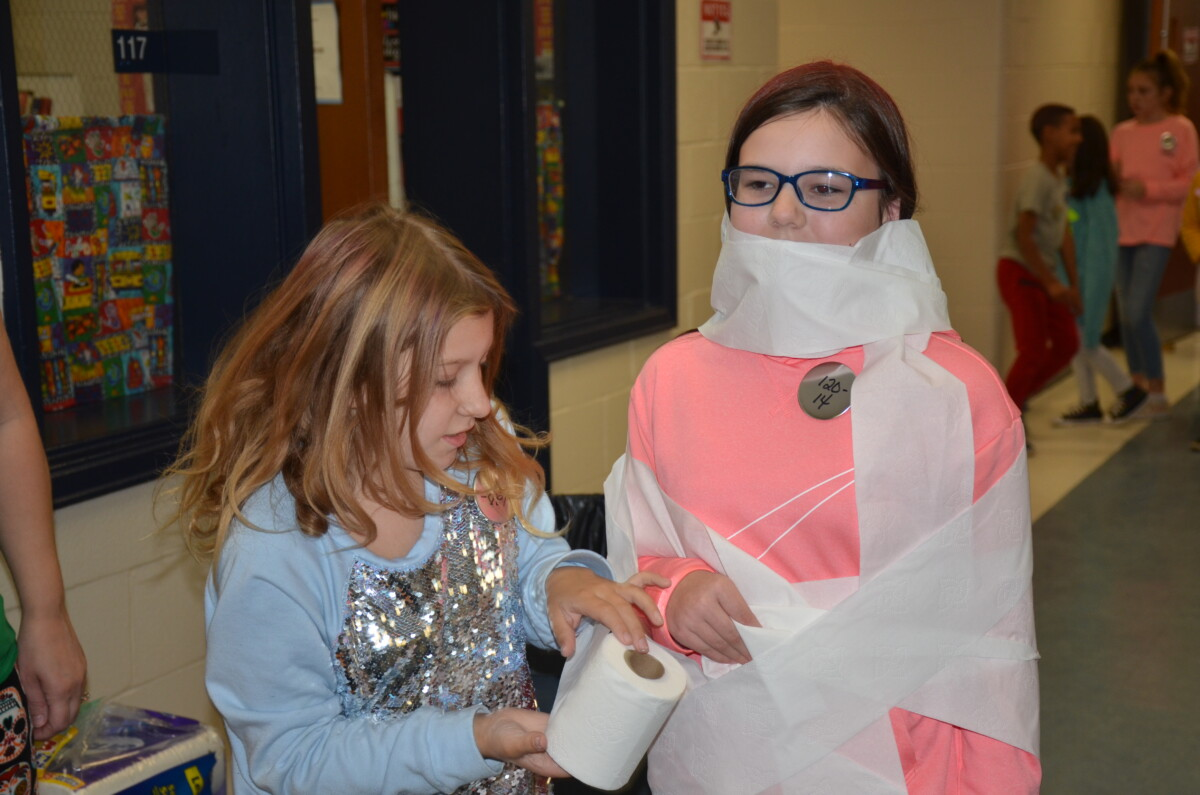 Students playing mummy game at the fall festival