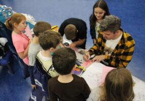 Students gather around an artist at career day at Central Elementary School.